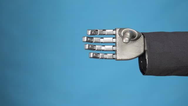 若い女性がサイボーグの灰色の機械腕を振る。2人のビジネスマンの握手。青い背景に手をクローズアップ。 - 指点の映像素材/bロール