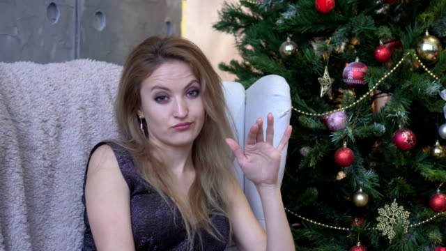 Young woman shaking head to reject, no, on christmas tree background video
