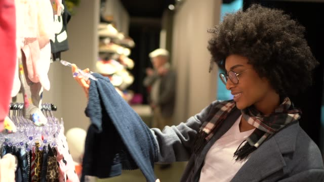Young woman shopping for baby clothes