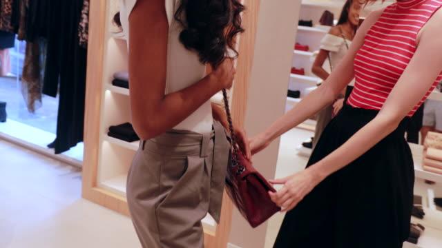 vídeos de stock, filmes e b-roll de jovem mulher comprando saco na loja - boutique