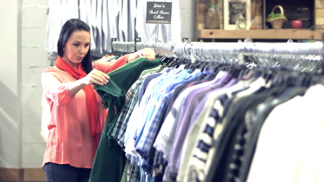 Young woman shopping for men's shirts in clothing store video