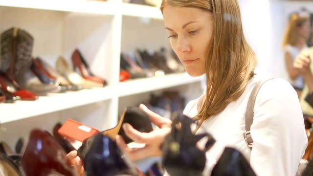 young woman shopping for shoes in mall. choosing stilettos. view through store window. rows of shoes - shoes fashion stock videos and b-roll footage