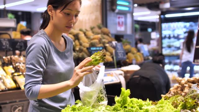 junge frau kauft frisches gemüse in supermarkt - supermarkt einkäufe stock-videos und b-roll-filmmaterial