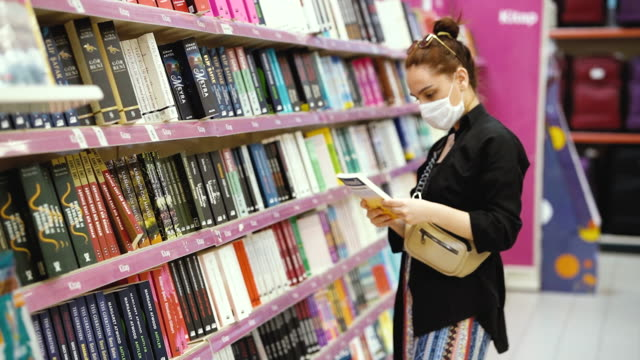Young woman shopping in a book section in the store and wearing protective medical mask video