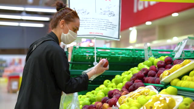 Young woman shopping in a grocery store and wearing protective medical mask video
