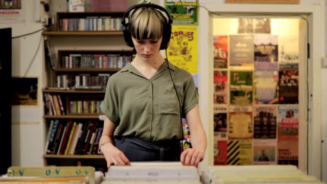 若い女性のレコード店でのショッピング - アナログレコード点の映像素材/bロール