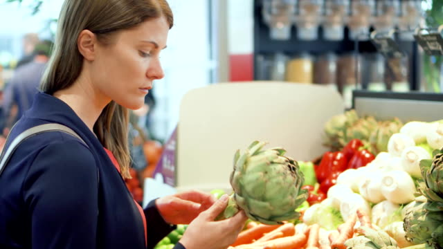 Young woman shopping in grocery store. Standing in vegetable department choosing fresh artichoke video
