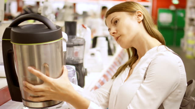 Young woman shopping in store buying kitchen appliances. Picking up thermos, choosing kettle Young woman shopping in store buying kitchen appliances. Picking up thermos. Kitchen appliances, white goods and electronics on background appliance stock videos & royalty-free footage