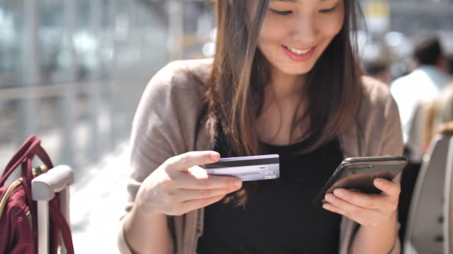 ung kvinna shopping på smart phone med kreditkort - kinesiskt ursprung bildbanksvideor och videomaterial från bakom kulisserna