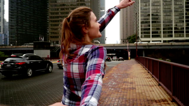 Young woman showing great view of modern city skyscrapers. Follow me concept video