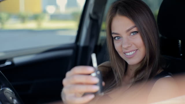 Young woman showing key to new car video