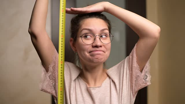 A young woman shows joy at her growth by holding a measuring tape next to her A young woman shows joy at her growth by holding a measuring tape next to her. The growth of a short woman and positive emotion short length stock videos & royalty-free footage