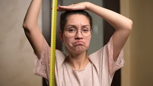 A young woman shows sadness at her height by holding a measuring tape A young woman shows sadness at her height by holding a measuring tape next to her. The growth of a short woman and negative emotion short length stock videos & royalty-free footage