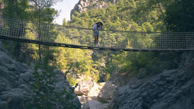 Young woman silhouette stands on long suspension bridge Young woman silhouette stands on long suspension bridge over large rocky canyon between hills against green dense forests under bright summer sunlight slow motion. suspension bridge stock videos & royalty-free footage