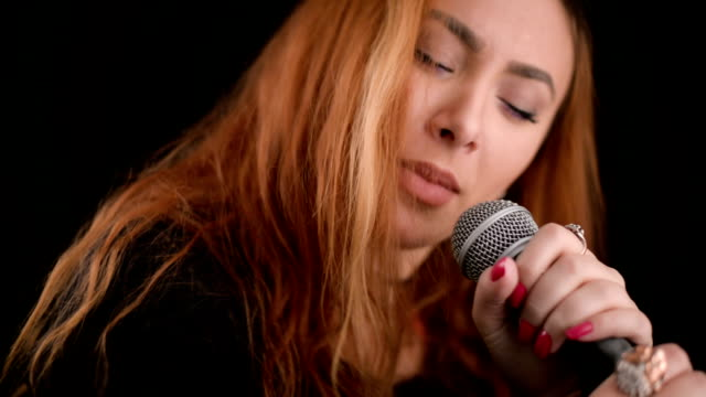Young woman singing in microphone video