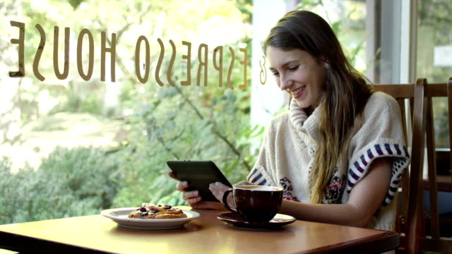 A young woman sits at a table in a cafe and looks at her tablet while drinking her coffee video