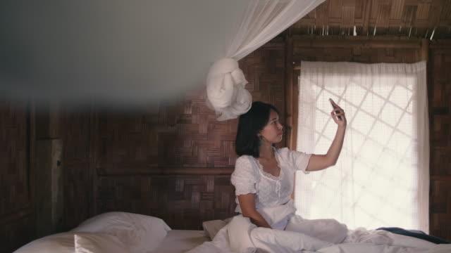 junge frau sitzt im weißen bett für selfie mit smartphone im schlafzimmer. - moskitonetz stock-videos und b-roll-filmmaterial