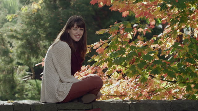 Young woman sits on a stone wall and laughs at the camera video