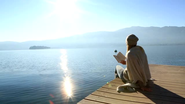 young woman sits on jetty above lake, reading book - gente serena video stock e b–roll