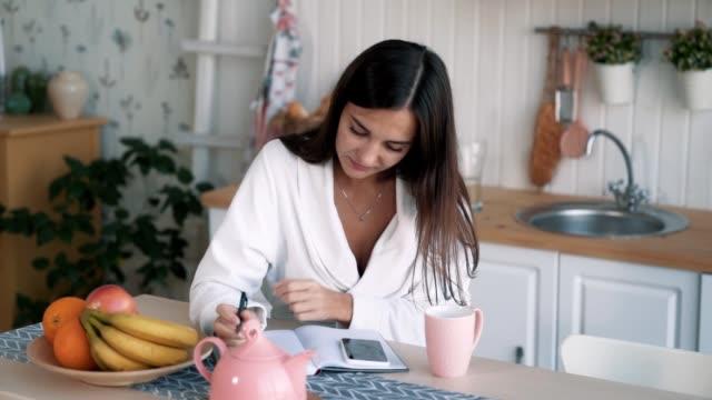 giovane donna si siede in cucina, fa appunti nel taccuino che distogli, al rallentatore - to do list video stock e b–roll