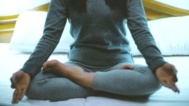 junge frau sitzt auf dem bett und macht meditation yoga vor dem schlafengehen in der nacht. - atemübung stock-videos und b-roll-filmmaterial