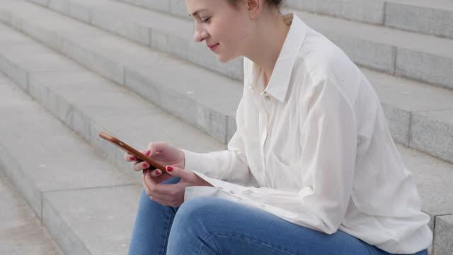 Mujer joven se sienta en los escalones con smartphone - vídeo