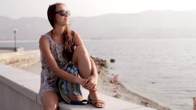 Young woman sitting and looking on the sea video
