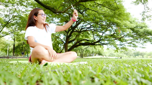 Young Woman Sitting and Using Smartphone in the Park video