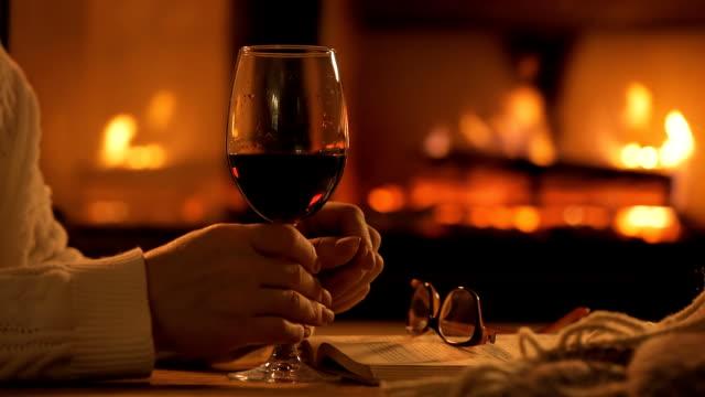 若い女性の家で暖炉のそばで座っていると、赤ワインを飲みます。 - ワイングラス点の映像素材/bロール