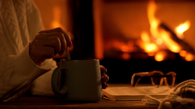 Young woman  sitting at home by the fireplace. Young woman  sitting at home by the fireplace. Woman stirs mug of cocoa with spoon. fireplace stock videos & royalty-free footage