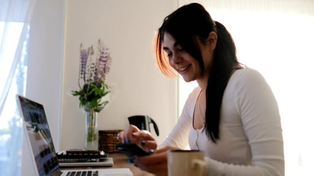Young Woman Sitting At Table Using Laptop Computer And Cell Smart Phone At Home Beautiful Girl Chatting Online In Morning Indoors video