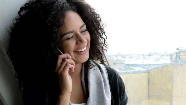 young woman sitting at window using smartphone - бразилец парду стоковые видео и кадры b-roll