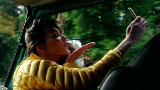 ung kvinna sitter i en van. blåser en kyss för en selfie - blåsa en kyss bildbanksvideor och videomaterial från bakom kulisserna