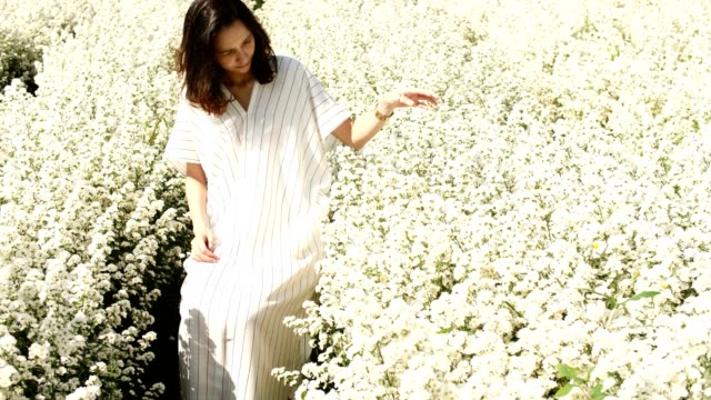 Young woman sitting in a white flower garden. video