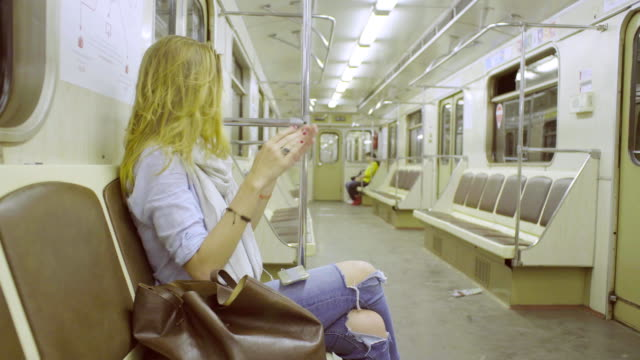 Young woman sitting in subway train Young woman sitting in subway train, listening music and dancing performer stock videos & royalty-free footage