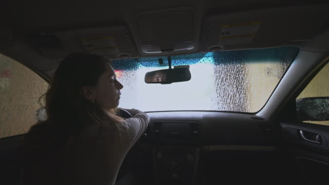 Young woman sitting in the car at the automatic car wash, when the car is cleaning. View from the car through the windshield.