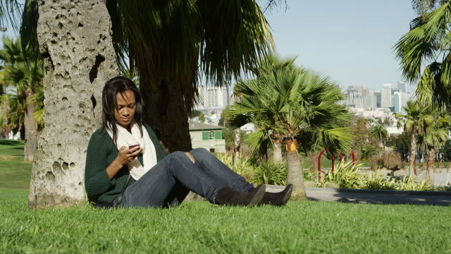 A young woman sitting in the grass, under a tree in a park during the day answers her cell phone and then gets up to leave video