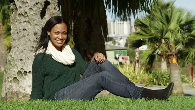 una giovane donna seduta in erba, sotto un albero in un parco durante il giorno, sorride alla macchina fotografica - viaggio d'istruzione video stock e b–roll