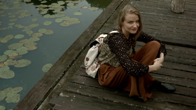 Young woman sitting near a lake on a wooden pier. video