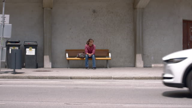 young woman sitting on a city bench with traffic - эскапизм стоковые видео и кадры b-roll