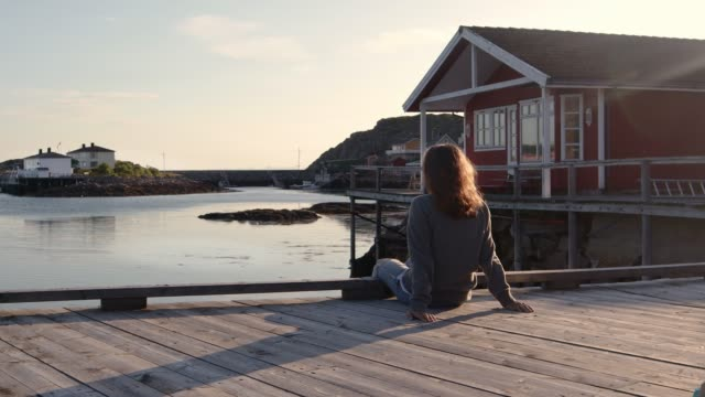 a young woman sitting on a pier at sunset time and enjoys the view. - capanna video stock e b–roll