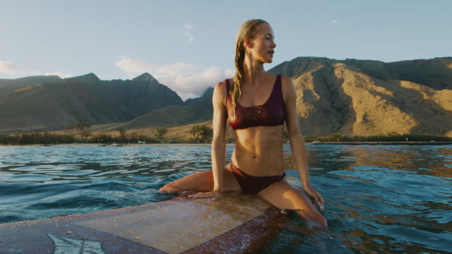 Young woman sitting on a surfboard at sunset video