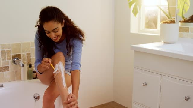 young woman sitting on bathtub waxing her leg with razor 4k 4k - depilacja filmów i materiałów b-roll