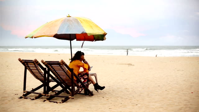Young woman sitting on deck chair on Calangute beach and using smartphone, Goa