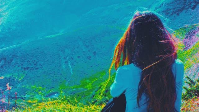 젊은 여자 잔디에 앉아서 휴식. 마운틴 뷰를 즐기고 있다. - 스톱 모션 스톡 비디오 및 b-롤 화면