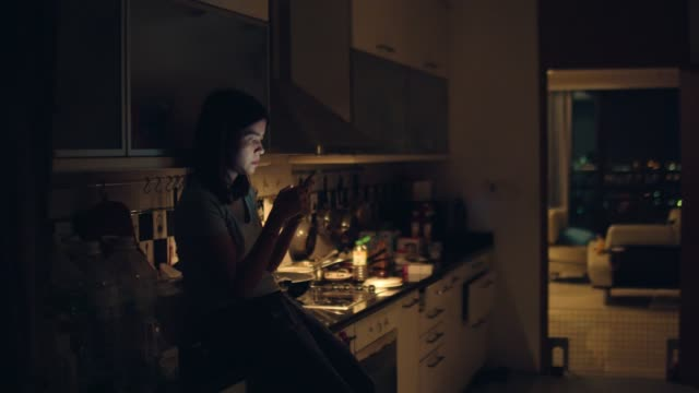 Young woman sitting on kitchen counter and using smartphone standing in kitchen at home in midnight.