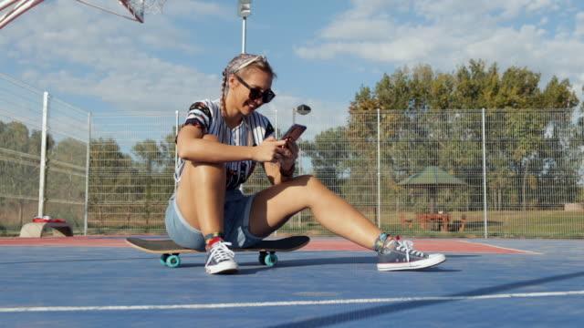 stockvideo's en b-roll-footage met jonge vrouw zittend op skateboard op basketbalveld en texting terwijl het nemen van een rust - 25 29 jaar