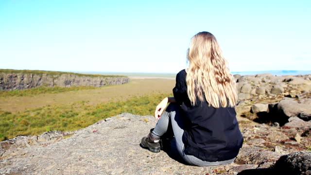 young woman sitting on the cliff edge in iceland - horseshoe stock videos & royalty-free footage