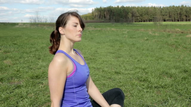 young woman sitting outdoors on grass and breathing video