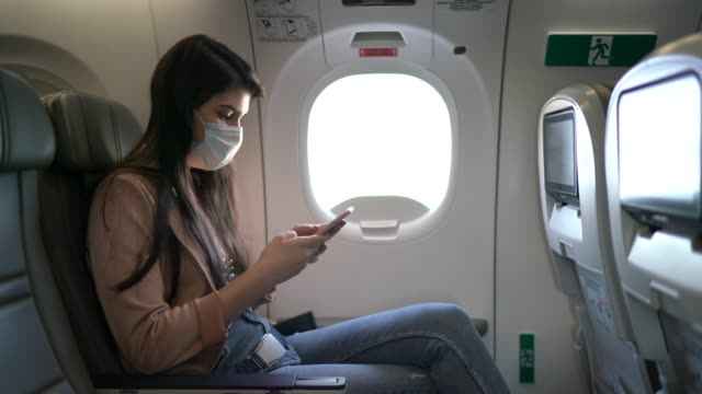 junge frau sitzt mit telefon auf dem flugzeugsitz tragen gesichtsmaske - travel stock-videos und b-roll-filmmaterial